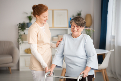 caregiver in uniform helping smiling senior woman with a walker