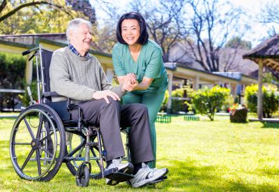 caregiver happy with senior man on wheelchair