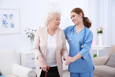 nurse and elderly women in light room