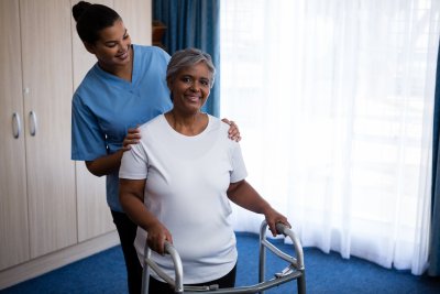 caregiver assisting senior woman in walking with walker